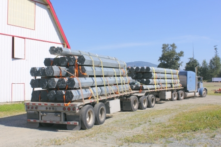 A semi trailer rig hauls steel pipes or poles