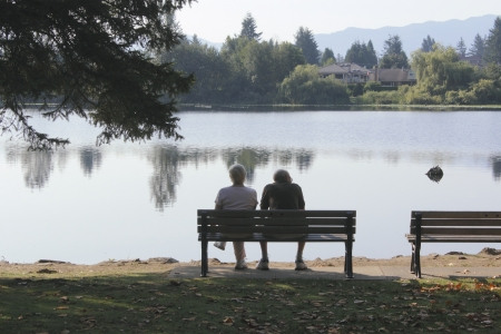An elderly couple sit on a bench by a placid lake