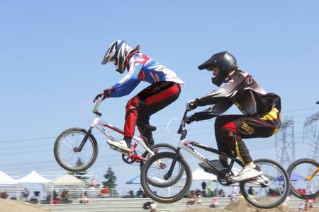 Twee kinderen springen een heuvel bij een lokale BMX wedstrijd in Abbotsford, British Columbia op 11 augustus 2012.
