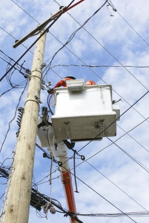 linemen: A power pole is fixed with new electric powerlines