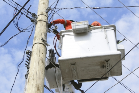 linemen: Linemen hook-up new powerlines for a hydro pole Stock Photo