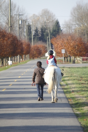 escorting: A mother escorts her child on horseback who is wearing safety equipment