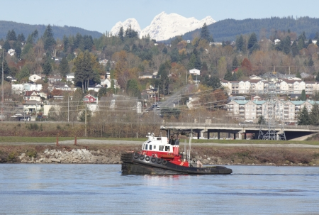 A small, modern tug hauls a barge past the small Canadian community of Mission, British Columbia Stock Photo - 16494165