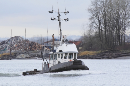 A tug boat motors past an industrial area of the river photo