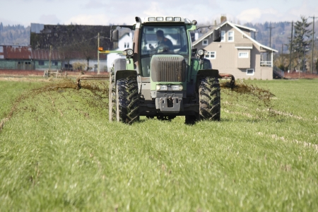 A farmer prepares his or her field by fertilizing the field with manure  photo