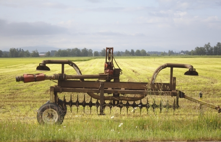 farm implement: An old farm implement stands before a bright yellow field of hay on a Washington farm