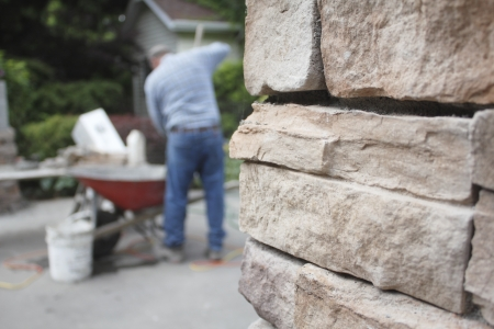 A bricklayer mixes cement in an outdoor residential site