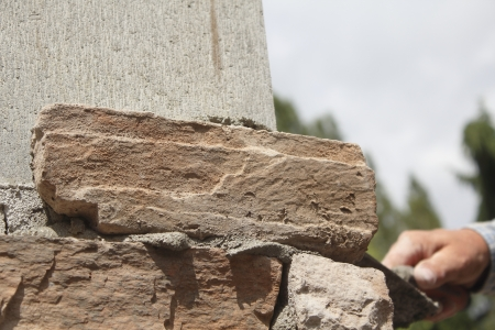 Mortar and brick are applied to a form that will make for a decorative fence in a residences driveway   photo