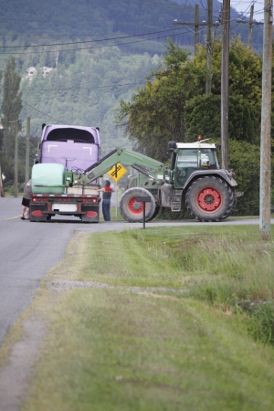 retrieves: A tractor retrieves the last hay bale from a delivery truck   Stock Photo