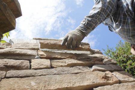 reaches: A mason reaches out to set a stone or brick in place