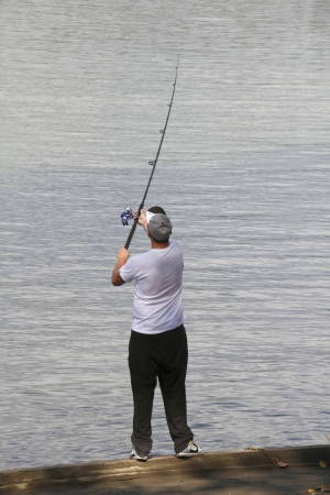 An avid fisherman casts his reel into the river  photo