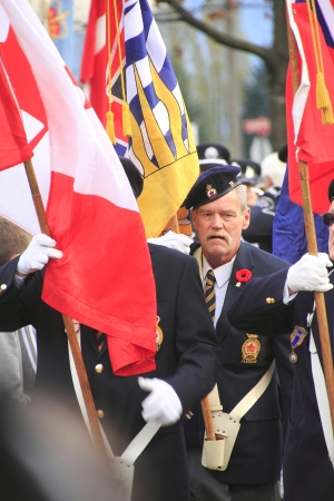 A senior war vetran carries the Canadian flag during Remembrance Day ceremonies