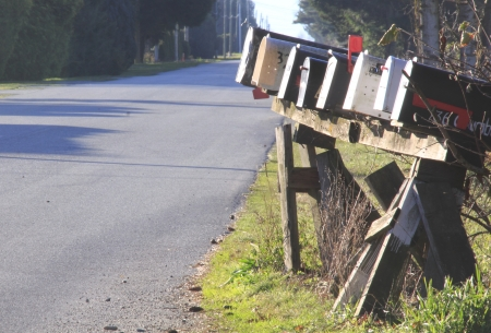 lined up: Rural mailboxes lined up in a row beside a road  Stock Photo