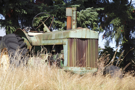 An old, abandoned and faded tractor is left neglected and abandoned in tall summer grass