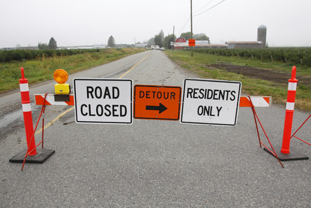 Various construction signs set up on a rural road