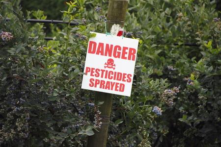 Een bord waarschuwt het publiek dat de bosbessen gewas is bespoten met bestrijdingsmiddelen