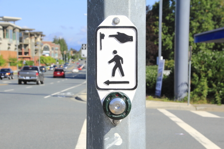A button is used for pedestrians to safely cross the street when activated.