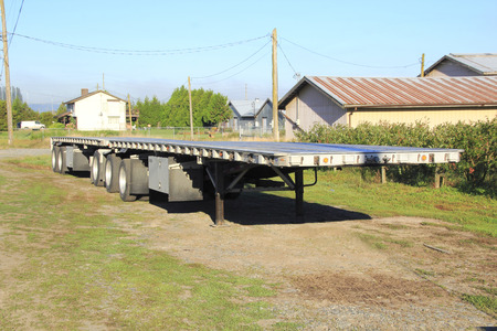 flatbed truck: A parked double flatbed trailer used for heavy duty hauling.
