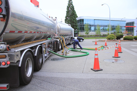 가솔린을 담고있는 두 개의 컨테이너가있는 트럭을 상업용 주유소에 보관 탱크를 채우는 데 사용합니다. 스톡 콘텐츠
