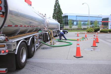 Een vrachtwagen met twee containers met benzine wordt gebruikt om te vullen met tanks bij een commerciële benzinestation. Stockfoto
