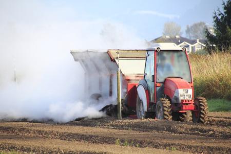 nutrientes: Un agricultor se dispersa una nube de nutrientes en un campo en preparaci�n para las plantas de ar�ndanos. Foto de archivo