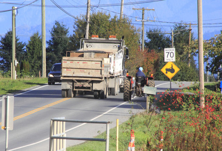 careless: A dump truck crosses a double line cutting off on-coming traffic in an attempt to pass a tractor. Editorial