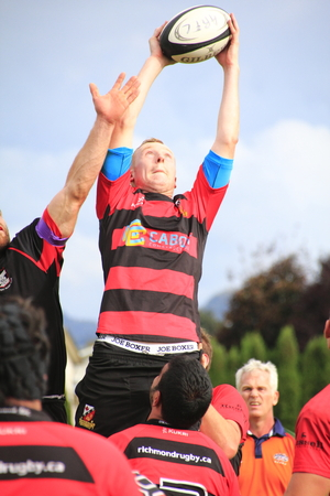 A Canadian rugby player catches the ball after a line-out pass.