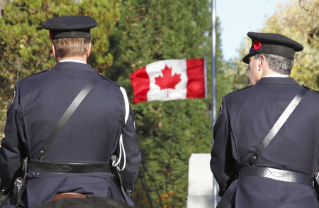 two and a half: Two Canadian policemen mounted on their horses face a flag flying at half staff. Editorial