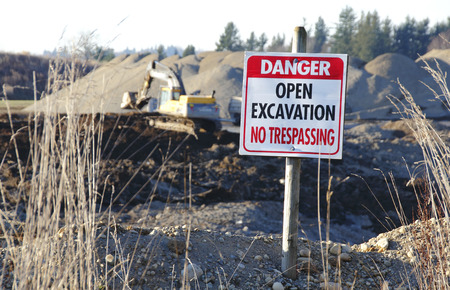 an excavation: A sign warns of an open excavation and no trespassing