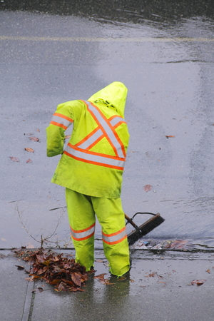 Een werknemer in een veiligheid pak reinigt puin van de opening van een riool na zware regenval.