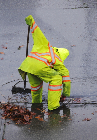 A worker in a safety suit cleans debris from the opening of a sewer after heavy rains. Banque d'images