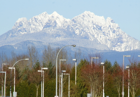 snow capped mountain: Street lights swarm beneath a snow capped mountain as Urbanization slowly consumes nature.