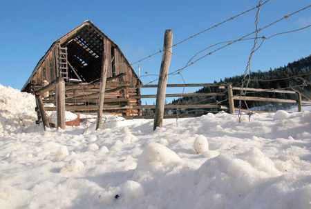 Low angle view of an old, rundown barn in winter
