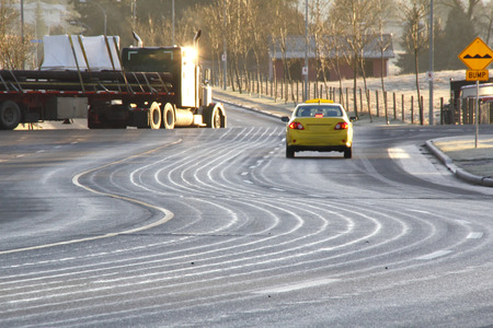A special liquid has been spread across an icy road to prevent cars from slipping.