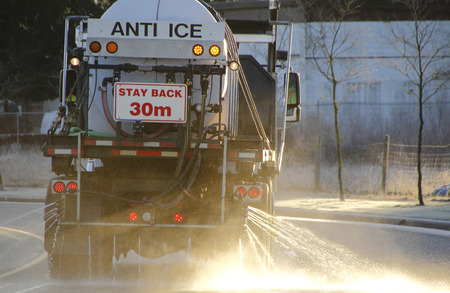 A truck uses special liquid to spread across an icy road.