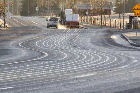 Liquid has been applied to a dangerous, icy road to prevent cars from slipping.