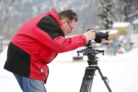 Professional photographer carefully frames camera preparing to take a shot