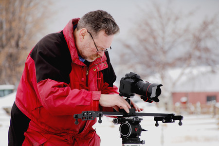 A professional photographer uses a slider to record a clip. Фото со стока