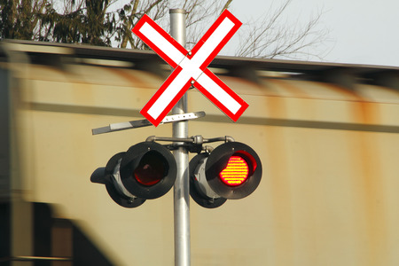 symbolization: A blinking light and sign warns motorists of a speeding train passing through.