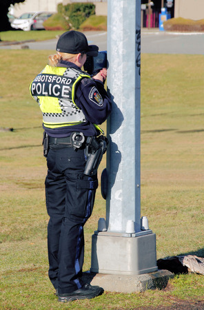 A female police officer holds a radar gun checking for speeding vehicles.