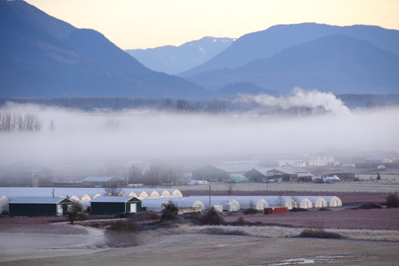 rural community: A fog bank hovers above a small rural community in a valley.