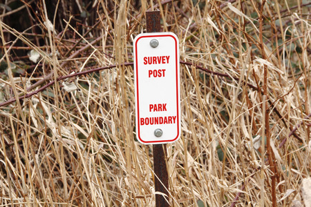 signage outdoor: A sign indicates where a park boundary is located.