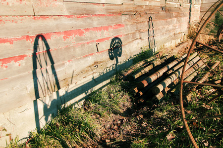 farm implement: The shadow of a turn of the century Horse Rake is cast on the wall of a barn. Stock Photo