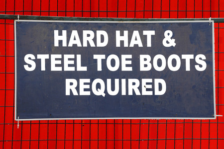 steel toe boots: A sign on a construction site requires a hard hat and steel toe boots.