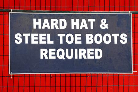 Un letrero en un sitio de construcción requiere un sombrero y botas de punta de acero duro. Foto de archivo - 35821377