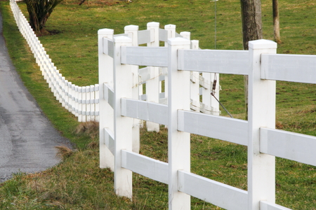 defines: A long and winding fence defines the private property border. Stock Photo