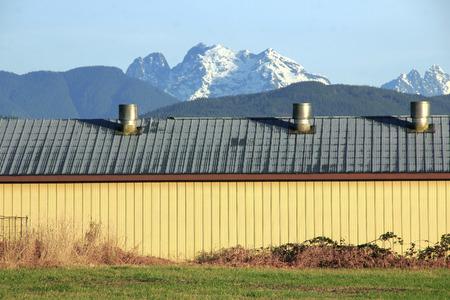 snow capped: Un gallinero metal moderno con monta�as cubiertas de nieve en el fondo. Foto de archivo