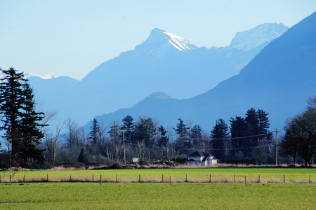 snow capped mountain: A snow capped mountain overlooks a valley