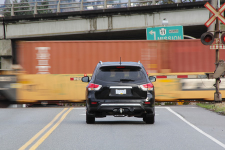 sitting on the ground: A vehicle waits as a speeding train passes through a crossing.