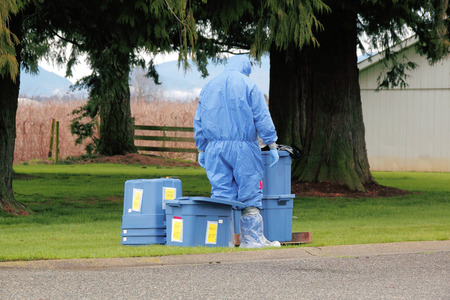 A technician in full Hazmat suit prepares to enter a chicken barn to test for Avian Influenza. Stock Photo